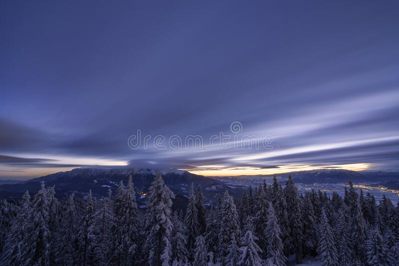 Beautiful landscape snow mountains at night on blue cloud and star background. Piatra Craiului mountains, view from Postavaru stock photos