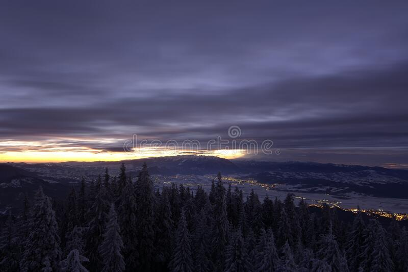 Beautiful landscape snow mountains at night on blue cloud and star background. Piatra Craiului mountains, view from Postavaru royalty free stock image