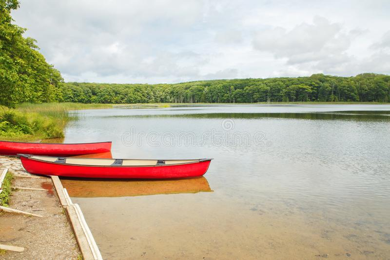 Canada forest park nature with red kayaks canoe boats by water stock photos