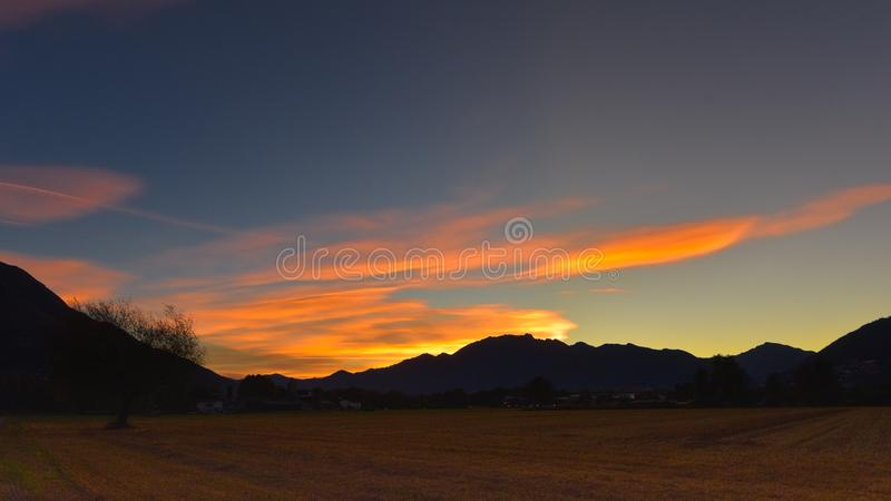Beautiful landscape of a sunset over the countryside. With field, green and blue sky royalty free stock image