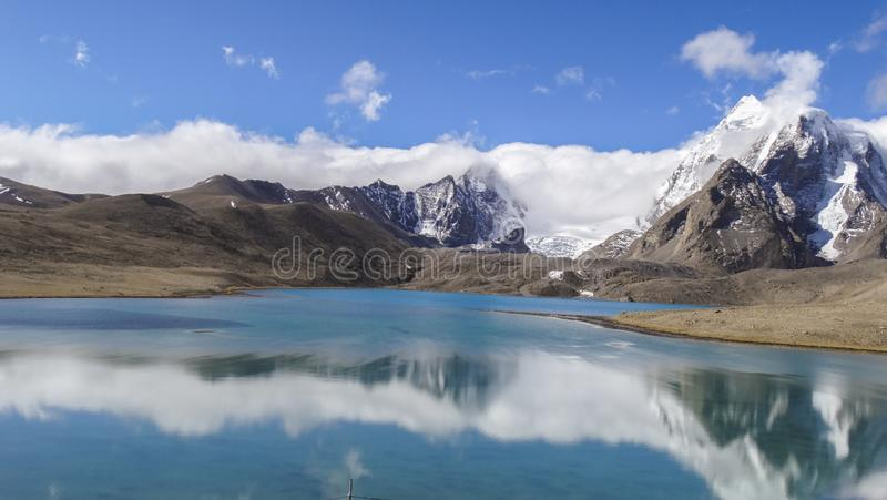 Beautiful landscape of vast sky mountain and lake with reflection of cloud in clean greenish water. In nature with wonderful panoromic view stock images