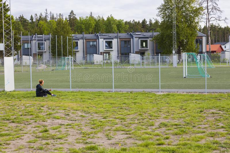 Beautiful landscape view of football playground . Woman sitting on ground and talking on mobile. Sweden. Europe. Uppsala. 06.04.2020 stock photo