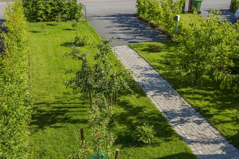 Beautiful landscape view of private garden. Green grass lawn, peony bush, apple tree, cherry tree. Gorgeous backgrounds royalty free stock image
