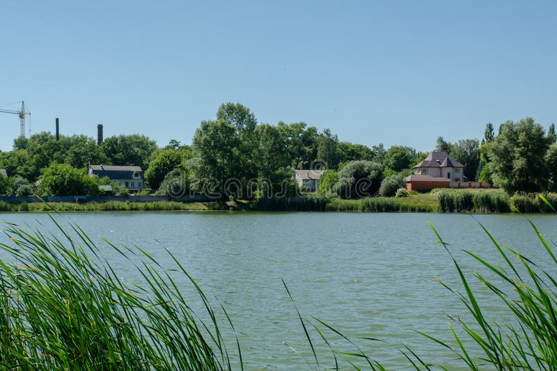 Beautiful landscape view of the river`s bank with houses and trees stock photos