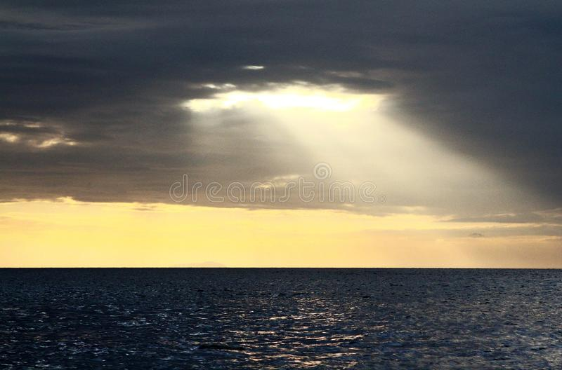 Beautiful Landscape view of sunlight shining from the dark clouds to the sea stock photography