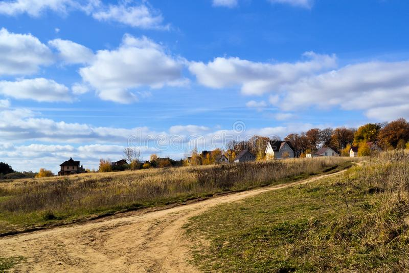 Beautiful landscape. Village near the autumn forest. Calm pastoral landscape. Autumn forest and cloudy sky royalty free stock photography