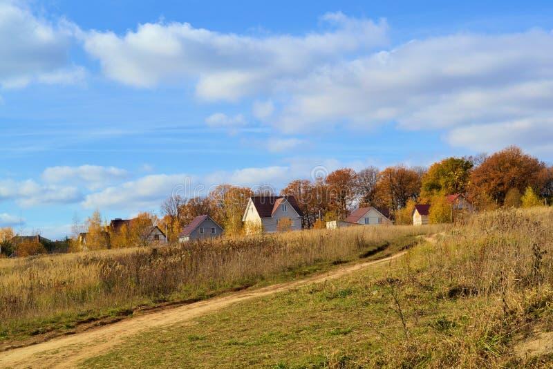 Beautiful landscape. Village near the autumn forest. Calm pastoral landscape. Autumn forest and cloudy sky stock images