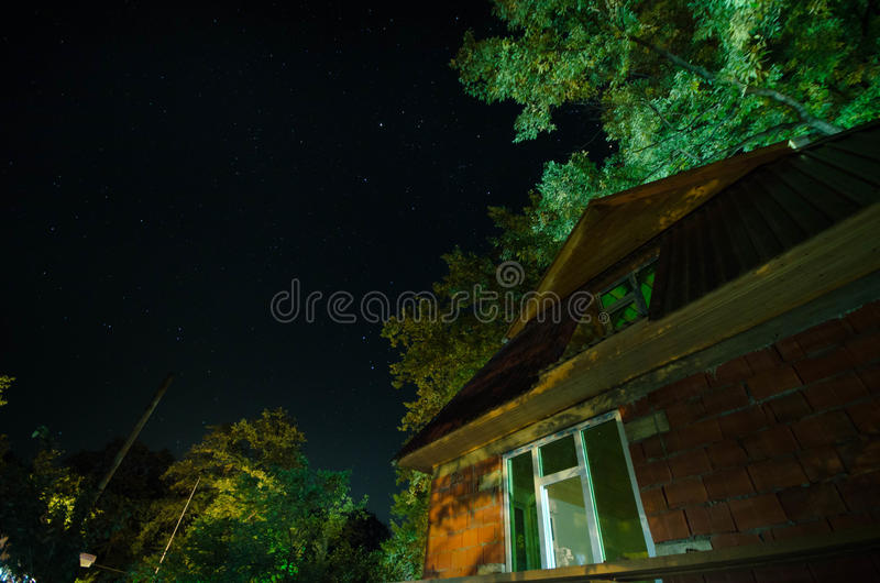 Beautiful landscape village street with buildings and trees and big full moon at the night sky. Big Caucasus . stock photo