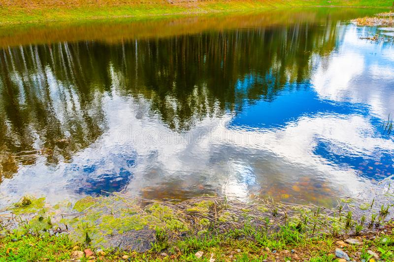 White clouds and blue sky are reflected in the lake stock photo