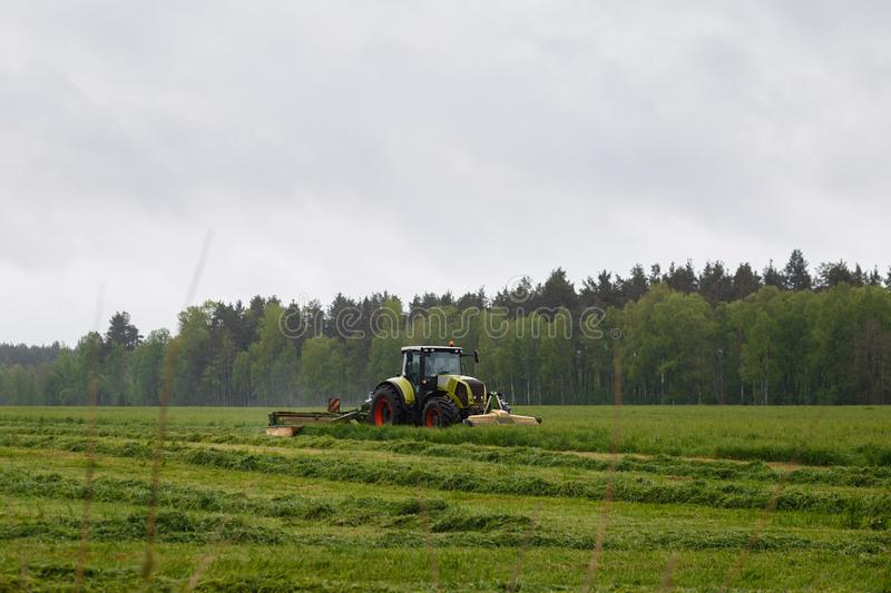 Beautiful lansdscape with haymaking. Is mowing the grass on a green field royalty free stock photo