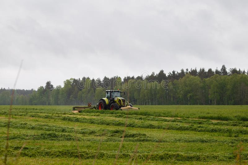 Beautiful lansdscape with haymaking. Is mowing the grass on a green field stock photos