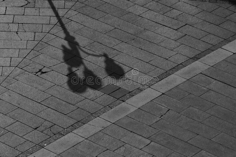 A beautiful lantern with 4 shades makes a shadow on the granite pavement. A beautiful lantern with 4 shades, decorated with decorative elements, casts a small royalty free stock images