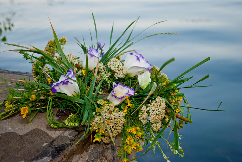 Beautiful large bouquet of flowers wreath lies on the stones of the parapet on the background of the river Ivan Kupala. One beautiful big bouquet of a wreath of stock photo