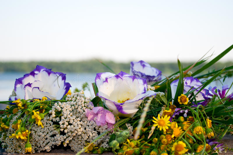 Beautiful large bouquet of flowers wreath lies on the stones of the parapet on the background of the river Ivan Kupala. One beautiful big bouquet of a wreath of royalty free stock photos