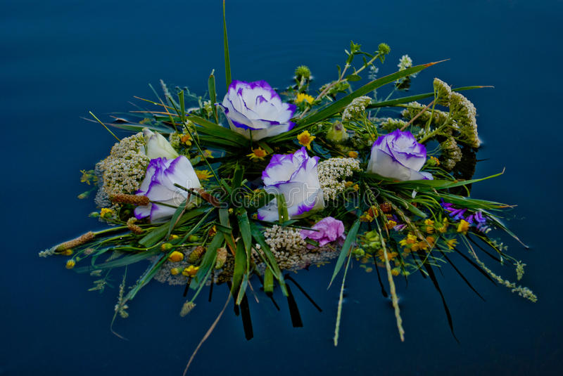 Beautiful large bouquet of flowers wreaths along the river calm water of Ivan Kupala. One beautiful large bouquet of a wreath of white purple yellow beautiful stock photography