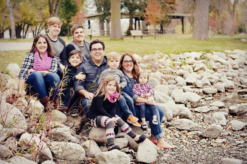 Beautiful large family sitting on rocks. A large family consisting of a mom, dad and seven children, four boys and three girls, sitting on some rocks in a park royalty free stock images