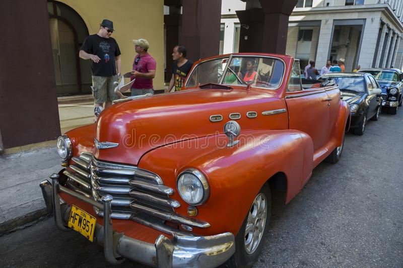 Beautiful large red classic car in busy Havana street royalty free stock images