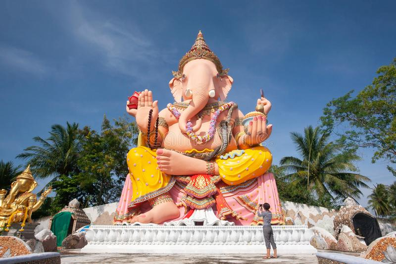 Beautiful large statue of Lord Ganesha, female asian standing and taking photo with camera at the Lord Ganesha. Narathiwat, stock photography