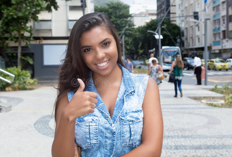 Beautiful latin american woman in jeans jacket showing thumb royalty free stock photo