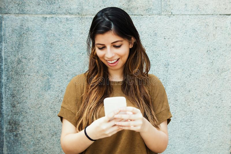 Beautiful latin american young adult woman sending message with royalty free stock photos