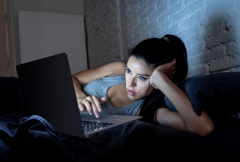 Pretty latin woman bored and addicted to her device in bed. stock images