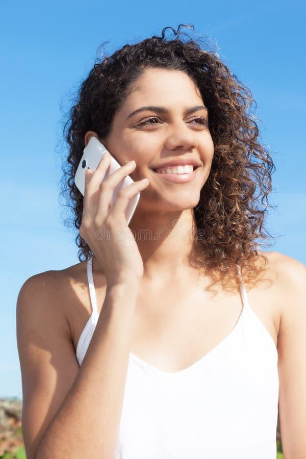 Beautiful latin woman speaking at phone stock image