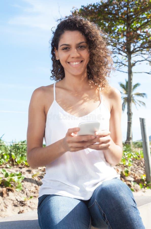 Beautiful latin woman typing message at phone royalty free stock image