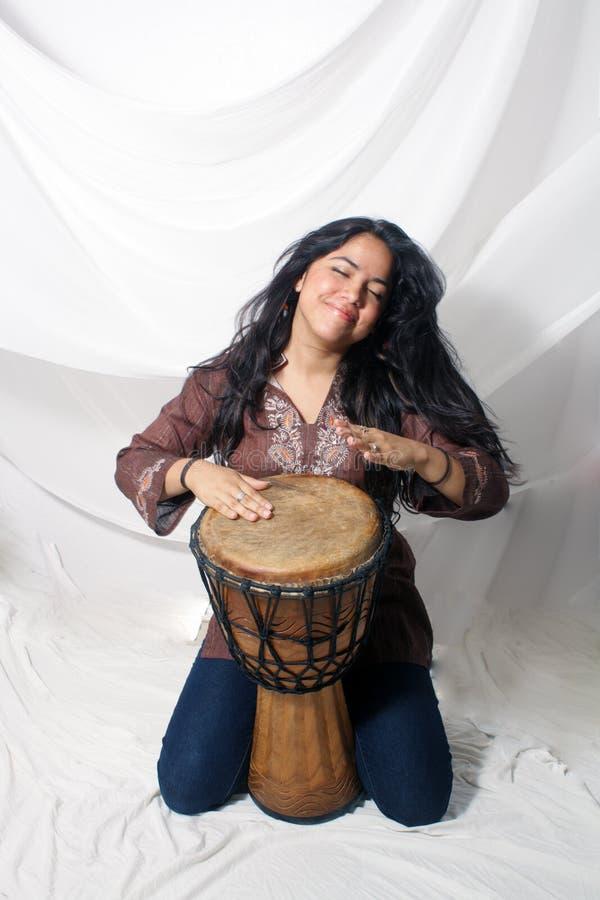 Beautiful Latina playing a Djembe Drum (1) royalty free stock photography