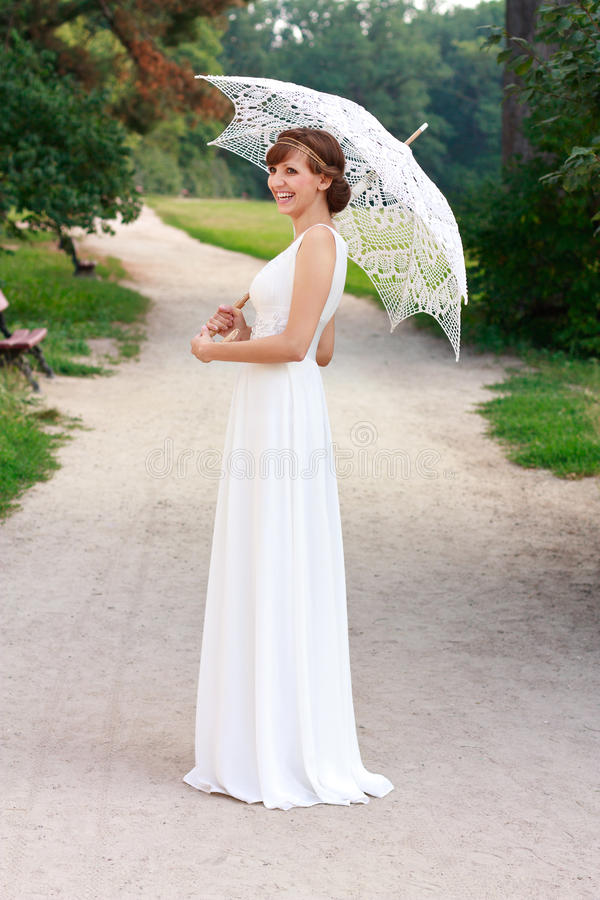 Beautiful laughing bride with decorative umbrella. Beautiful happy laughing bride in white dress with decorative umbrella against background green nature. In a royalty free stock image