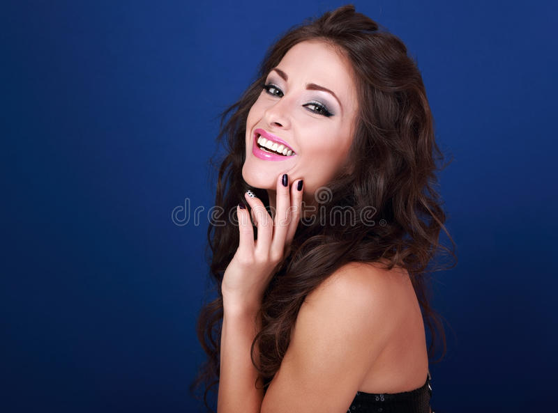 Beautiful laughing makeup woman with long volume hairdo and mani. Cured nails on bright blue background looking happy stock images