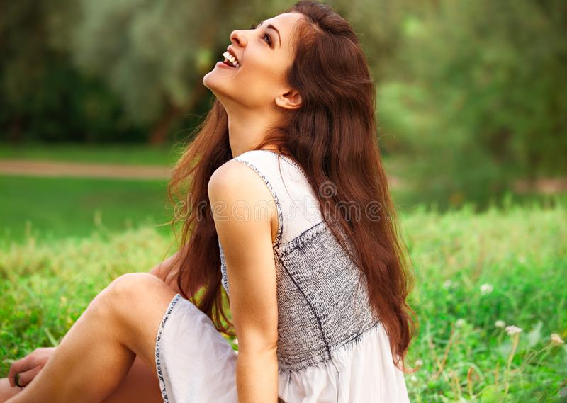 Beautiful laughing young woman with long hair sitting on the grass and looking up on summer green background. Closeup stock photography