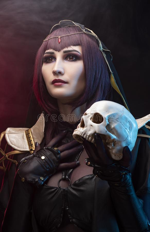 A beautiful leggy busty cosplay girl wearing an erotic leather costume poses holding fake human skull in her hands on a dark stock photo