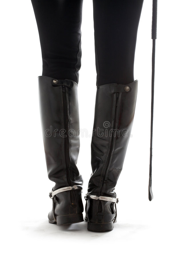 Beautiful legs in black leather horseman boots with riding-crop stock photo