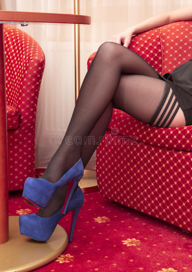 Beautiful legs in black stockings and in high heels stock images