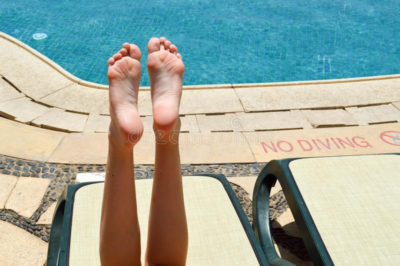 Beautiful legs, girls feet, women on the background of a deckchair and pool on a tropical warm exotic seaside resort, summer stock image