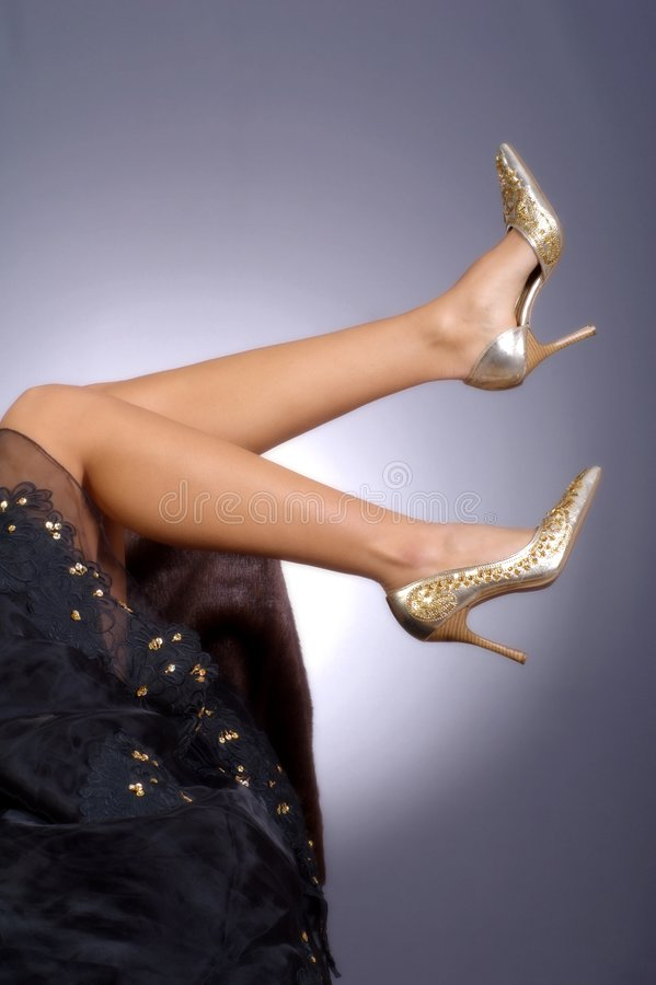 Beautiful legs with golden heels stock images