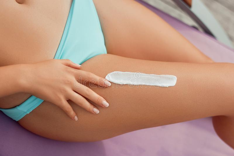Beautiful Legs  with Sunscreen. Skin Care. Woman Applying Sun Cream On Skin on Legs. Sun cream on Feet. Epilation Laser or Shaving Concept royalty free stock photos