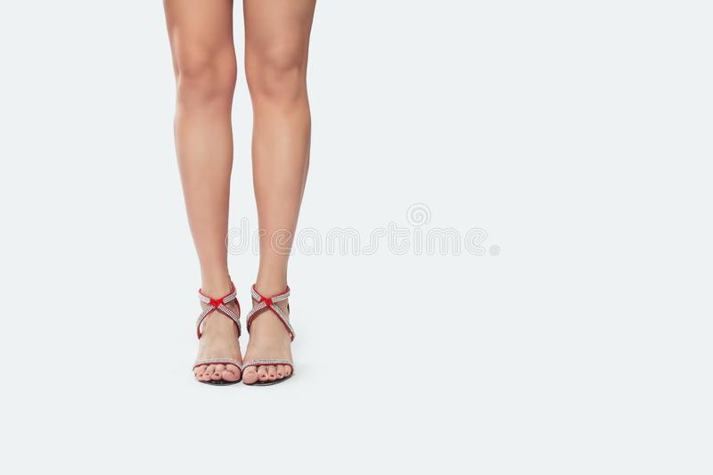 Beautiful legs woman in red high heels shoes standing on white background royalty free stock images