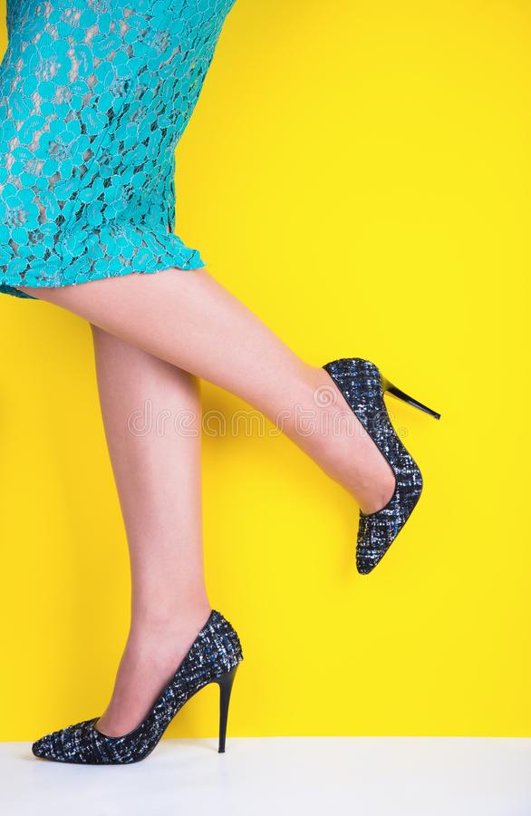 Beautiful legs of young woman in colorful skirt and black shoes with high heels on vibrant yellow background. Studio shot with copy space stock photos