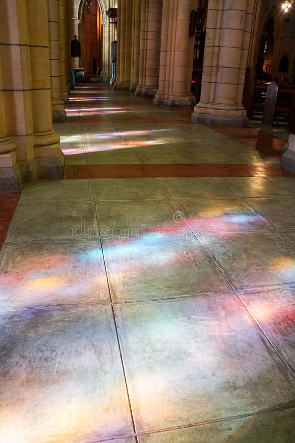 Beautiful light cast between colums by stained glass windows. Beautiful coloured light cast by stained glass church windows onto the flagstone floor stock photography