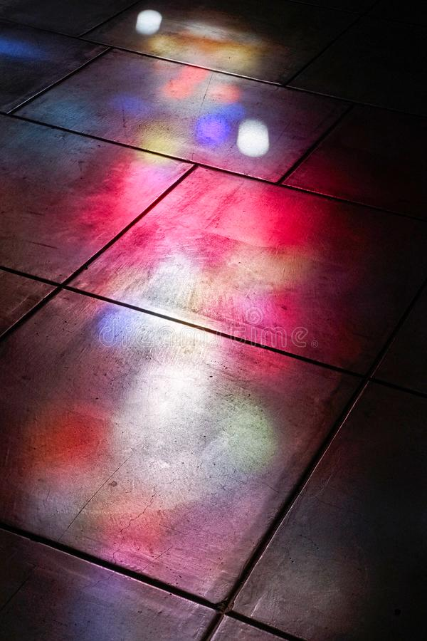 Beautiful light cast by stained glass windows. Beautiful coloured light cast by stained glass church windows onto the flagstone floor stock photo