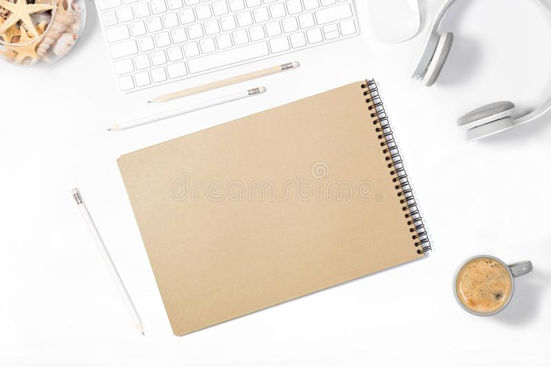 Beautiful light minimalistic mockup. White keyboard, mouse, headphones, pencils, sketchbook, vase with seashells and cup of cofee. Beautiful light minimalistic royalty free stock image