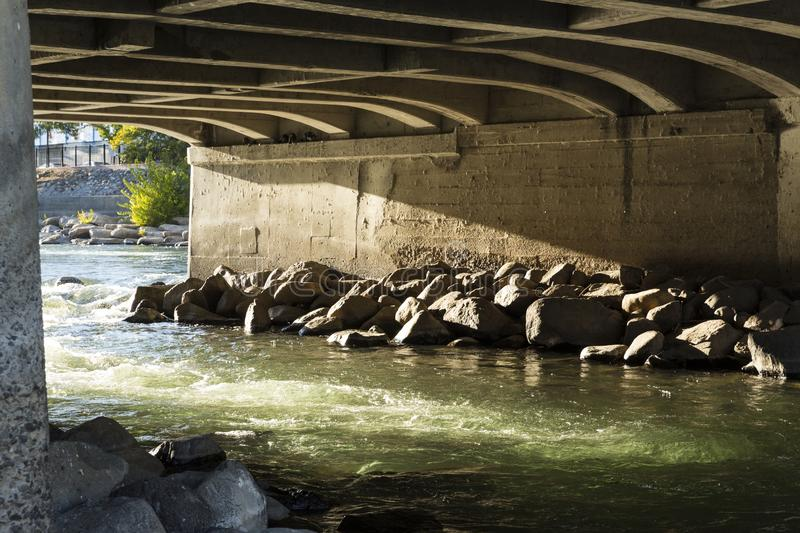 Beautiful light over green rushing water under a bridge on the Truckee royalty free stock images