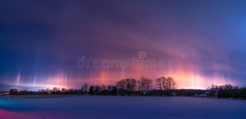 Beautiful light pillars in the winter. Panoramic. Beautiful show of light pillars on a cold, snowy winter evening royalty free stock photos