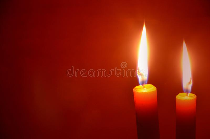 Beautiful light of wax candles on red black ground royalty free stock photography
