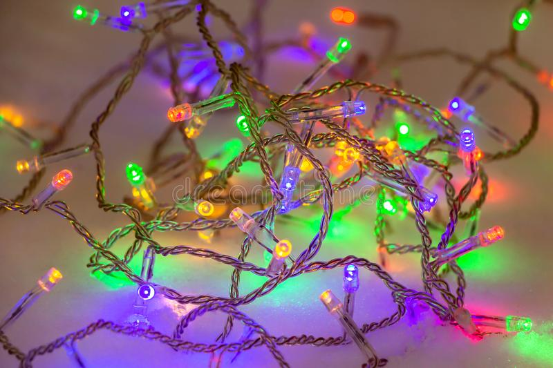 The beautiful lights garlands of burning colorful lamps are on a snow background. In the holiday evening royalty free stock images