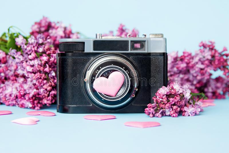 Beautiful lilac bouquet and retro photo camera on a blue background.  stock photos