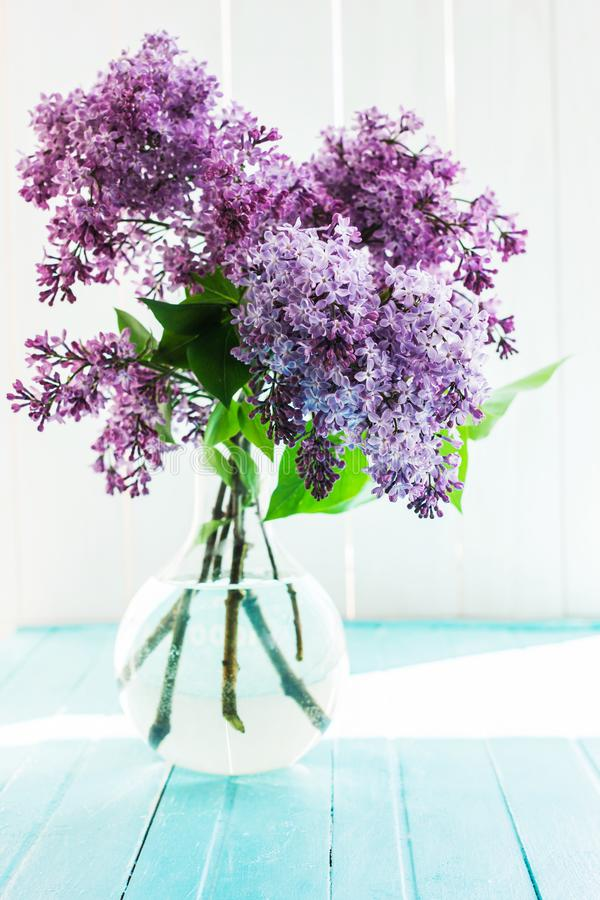 Beautiful lilac flowers in a clear glass vase on the table in front of the window stock photos