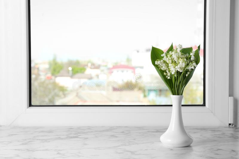 Beautiful lily of the valley bouquet in vase on windowsill. Space for text royalty free stock image