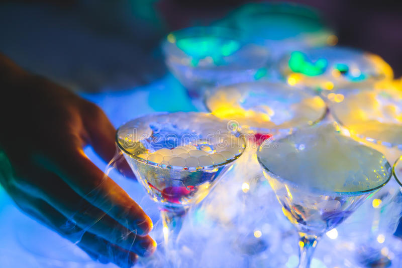 Beautiful line of different colored alcohol cocktails with smoke on a Christmas party, tequila, martini, vodka, and others on part. Beautiful line of different royalty free stock photos